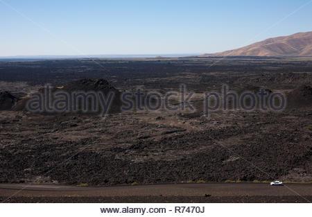 Coche blanco conduce a los cráteres de la Luna monumento nacional y preservar, Arco, Idaho, EE.UU. Imagen De Stock