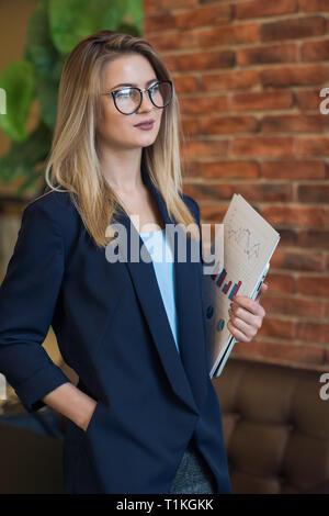 Mujer con gafas, holding de negocios con mesas de papel Imagen De Stock