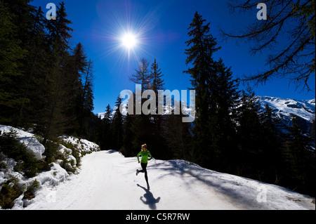 Un corredor corriendo en montañas nevadas. Imagen De Stock