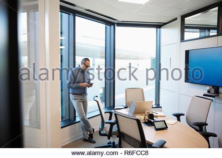 Empresario utilizando smart phone en la sala Imagen De Stock