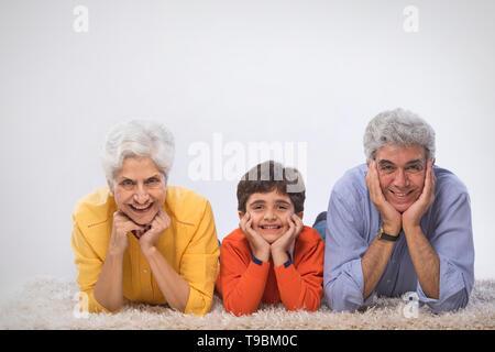 Los abuelos con su nieto acostado sobre una alfombra Imagen De Stock