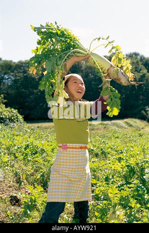 Chica recogiendo un rábano japonés Imagen De Stock