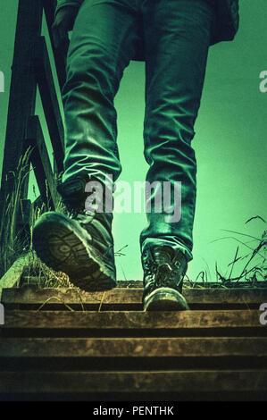Cierre de piernas caminando por las escaleras de madera Imagen De Stock