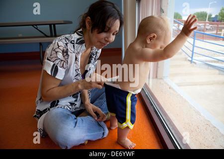 La madre del niño tira del pañal para verificar si necesita cambiar. Imagen De Stock
