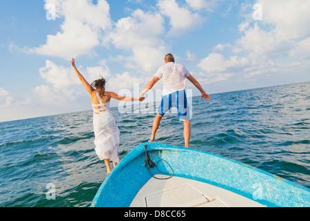 Vestida de hombre y mujer saltando de barco Imagen De Stock