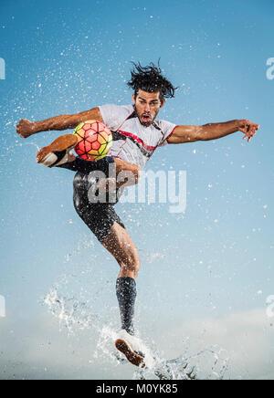Pulverización de agua sobre el hombre hispano pateando una pelota de fútbol Imagen De Stock