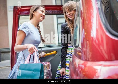 Las mujeres jóvenes entrar en taxi, llevar bolsas de la compra. Imagen De Stock