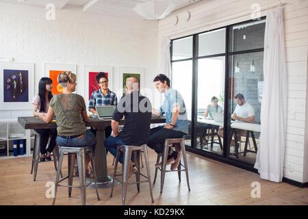 Compañeros de trabajo hablando en la oficina, otros trabajando en segundo plano. Imagen De Stock
