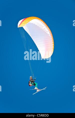 Una mujer piloto de parapente sonríe al volar su ala. Imagen De Stock