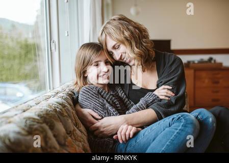 Madre e hija afectuoso abrazo en el sofá de la sala Imagen De Stock