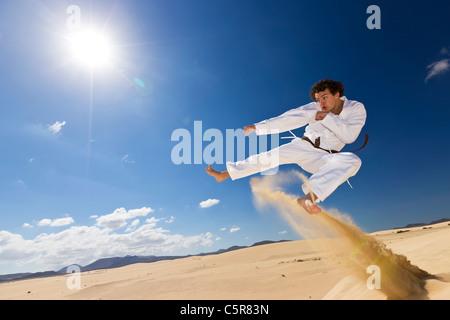 Un artista marcial formación sobre las dunas. Imagen De Stock