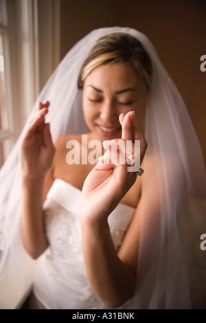 Novia de pie con los ojos cerrados y los dedos cruzados Imagen De Stock