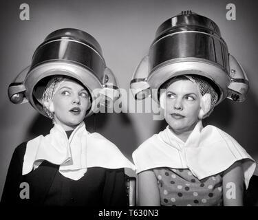 1950 Dos mujeres sentadas EN UN SALÓN DE BELLEZA SECADOR DE PELO llevar toallas redecillas para el cabello hablando chismes - s8918 DEB001 HARS EMOCIÓN PEINADO FEMENINO CONOCIMIENTOS AMAS DE CASA CHISMORREA PELO NOVIAS DEB001 REDECILLAS PARA EL CABELLO A MEDIADOS DE ADULTO DE MEDIADOS DE MUJER ADULTA COMPAÑERISMO adulto joven mujer EN BLANCO Y NEGRO la etnia CAUCÁSICA ANTICUADO DOS MUJERES Imagen De Stock