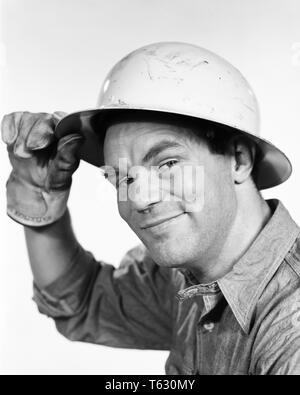 1960, trabajador de la construcción inclinando su sombrero duro mirando a la Cámara - s8756 HAR001 HARS B&W CONTACTO OCULAR BLUE COLLAR OCUPACIÓN HABILIDADES HABILIDADES DE CABEZA Y HOMBROS ALEGRE SU PROTECCIÓN SOMBRERO DURO EMPLEO ocupaciones sonríe gozosa cooperación empleado adulto medio hombre adulto medio TIPPING BLANCO Y NEGRO la etnia CAUCÁSICA HAR001 trabajando a la antigua usanza Imagen De Stock
