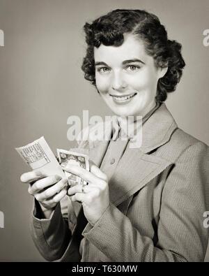 1940 1950 mujer morena sonriente mirando a la cámara la apertura de sobres de nómina y manteniendo el efectivo - s8493 HAR001 HARS MORENA LIBERTAD HABILIDAD TENTACIÓN SUEÑOS OCUPACIÓN FELICIDAD HABILIDADES PAYCHECK ALEGRE FORTALEZA PAGAR Y EMOCIÓN ORGULLO las ocupaciones sonríe gozosa compensación elegante mujer adulta joven EMPLEADO EN BLANCO Y NEGRO la etnia CAUCÁSICA HAR001 ANTICUADO Imagen De Stock