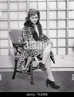 1930 1940 mujer vistiendo la piel de leopardo sombrero y untar CON GUARNECIDO DE PIELES tratando en el par de zapatos de tacón alto sentado en una silla - s7325 HAR001 HARS copia completa del espacio de media longitud longitud estimadas personas de piel morena de B&W SHOPPER COMPRADORES ESTILOS DE DESCUBRIMIENTO E INTENTAR RECORTAR PELT TACÓN elegante piel de leopardo poniendo en tratar sobre moda pieles dolorosa mujer adulta joven EN BLANCO Y NEGRO la etnia CAUCÁSICA HAR001 viejo dolor de pies Imagen De Stock
