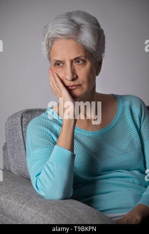 Retrato de mujer mayor pensando sentado en el sofá con la mano Imagen De Stock