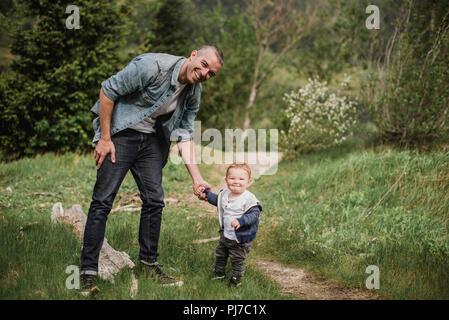 Retrato padre e hijo caminar sobre la senda cubierta de hierba Imagen De Stock