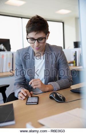La empresaria utilizando smart phone en escritorio de oficina Imagen De Stock