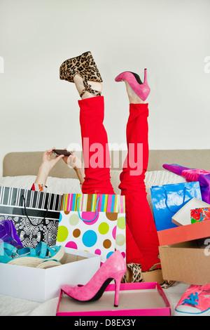 Mujer en la cama, rodeado de bolsas de la compra. Imagen De Stock