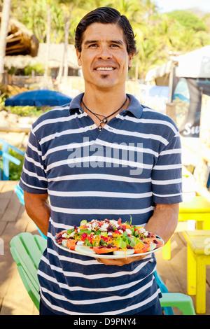 Hombre sujetando un plato de comida mexicana Imagen De Stock
