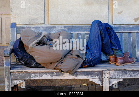 Hombre sin hogar duerme sobre el banco de madera, Cambridge, Inglaterra. Imagen De Stock