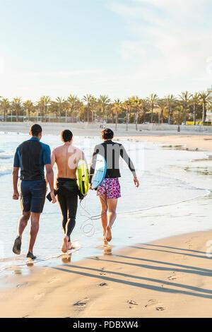 Surfistas masculinos caminando con tablas de surf en la soleada playa. Imagen De Stock