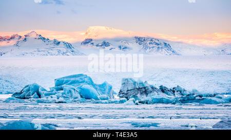 Témpanos que flotan en la Laguna glaciar Jokulsarlon al amanecer, con picos de montaña de fondo iluminado por el amanecer, en Islandia. Imagen De Stock