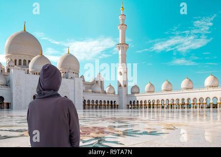 Foto del patio de la mezquita de Sheikh Zayed en Abu Dhabi con vista trasera de visitantes femeninas vistiendo un cabo obligatorias. Imagen De Stock