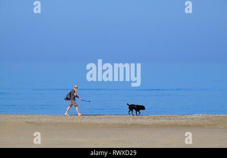 Persona caminando perro en la orilla, holkham Beach, North Norfolk, Inglaterra Imagen De Stock