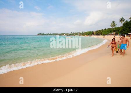 Los turistas que caminan en Unawatuna Beach Imagen De Stock