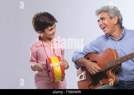 Abuelo tocando la guitarra y nieto batiendo el tambor Imagen De Stock