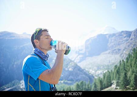 Excursionista de botella de agua potable, Mont Cervin, Cervino, Valais, Suiza Imagen De Stock