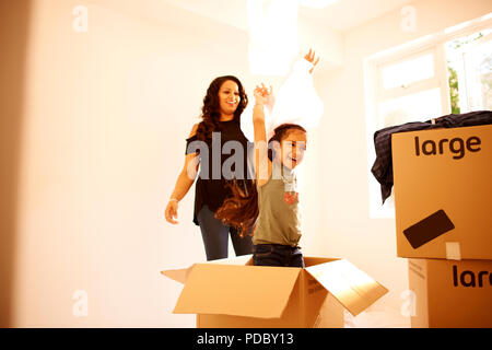 Juguetón, madre e hija entrando en casa nueva Imagen De Stock