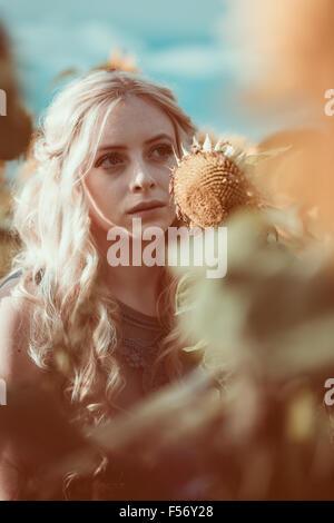 Hermosa mujer joven en un campo de girasol en hora dorada Imagen De Stock