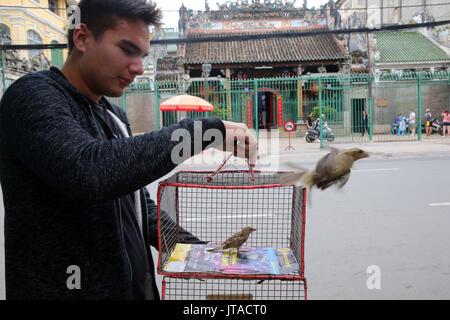 El hombre libera sparrow, Templo Taoísta, Phuoc An Hoi Quan Pagoda, Ho Chi Minh, Vietnam, Indochina, en el sudeste de Asia, Asia Imagen De Stock