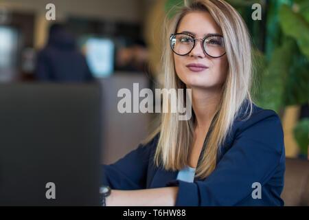 Una niña es un escritor que reflexiona sobre una historia o una historia de un libro. Retrato de una linda chica con gafas, sentado en un ordenador portátil. Imagen De Stock