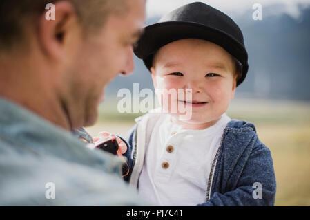 Retrato cute Baby Boy a lo largo de padre s hombro Imagen De Stock