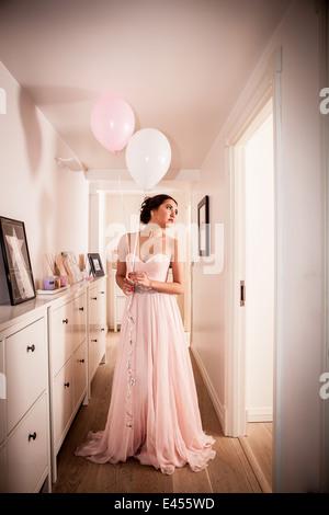 Mujer joven en vestido de noche soñar despierto en pasillo Imagen De Stock