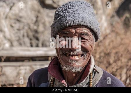 LANGTANG, Nepal- Noviembre 08, 2018: el viejo hombre de Nepal Langtang valle con curtido rostro posando para la cámara. Imagen De Stock