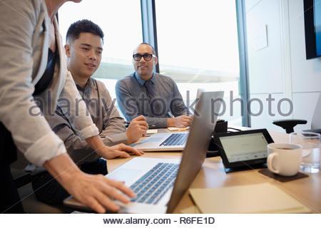 Las personas de negocios que trabajan en equipos portátiles en la sala reunión Imagen De Stock