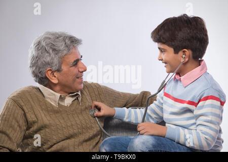Nieto escuchando abuelos heartbeat con estetoscopio Imagen De Stock