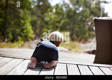 Baby Boy arrastrándose sobre porche Imagen De Stock