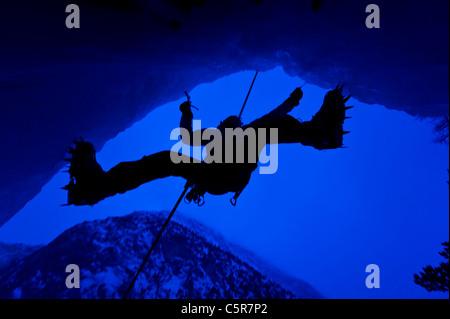 Escalador de hielo en la cueva con vistas a las montañas detrás. Imagen De Stock