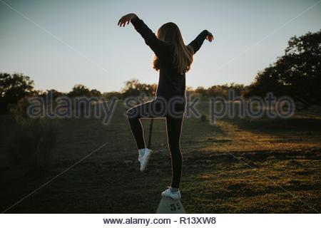 Disparo de longitud completa de una mujer posando en un campo durante la puesta de sol Imagen De Stock