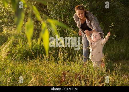 Madre con su hijo (18-23 meses) en pie por el árbol Imagen De Stock