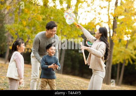 Una joven familia feliz jugando con burbujas en otoño woods Imagen De Stock