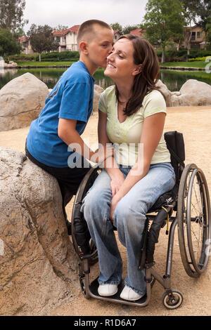 Hijo besar la mejilla de su madre discapacitada en silla de ruedas © Myrleen Pearson ...Cate Ferguson Imagen De Stock