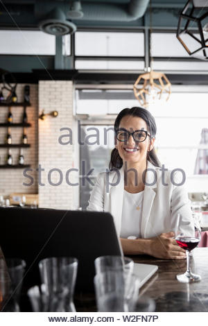 Retrato confianza empresaria trabajando en equipo portátil y beber vino en el restaurante Imagen De Stock