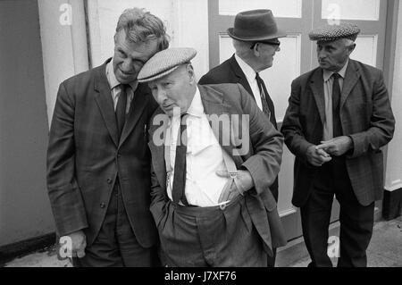 Amigos amistad grupo de hombres hablando juntos la vida aldeana Uk 1970 Inglaterra viendo la bella doncella de Holsworthy Imagen De Stock